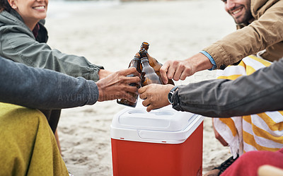 Buy stock photo Cropped shot of a group of young friends toasting with drinks at the beach