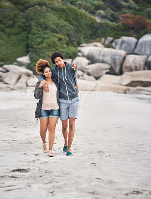 Buy stock photo Shot of an affectionate young couple enjoying their day at the beach
