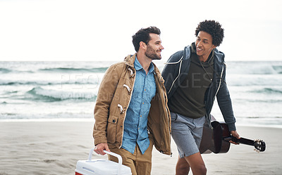 Buy stock photo Shot of two young men walking together along the beach