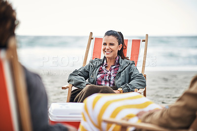 Buy stock photo Shot of a happy young woman hanging out with her friends at the beach