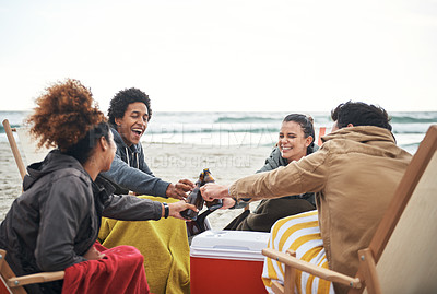 Buy stock photo Shot of a group of young friends toasting with drinks at the beach