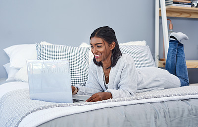 Buy stock photo Shot of an attractive young woman using a laptop and chilling on her bed in her bedroom at home