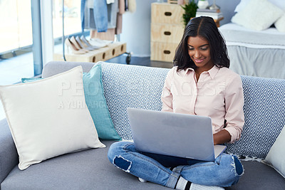 Buy stock photo Shot of an attractive young woman using a laptop while chilling on the sofa in the living room at home
