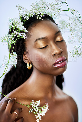 Buy stock photo Studio shot of a beautiful young woman posing amongst delicate flowers