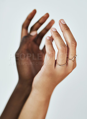Buy stock photo Cropped studio shot of two women touching hands against a gray background