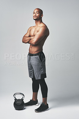 Buy stock photo Studio portrait of an athletic young man standing with his arms crossed against a grey background