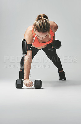 Buy stock photo Studio shot of an athletic young woman working out with dumbbells against a grey background