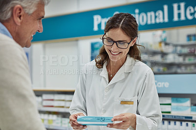 Buy stock photo Shot of a young pharmacist helping a customer in a chemist