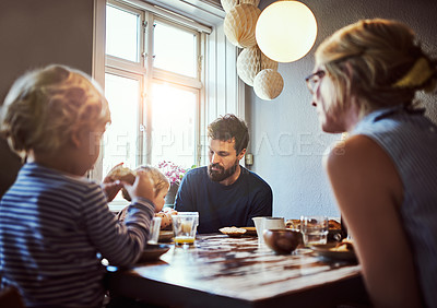 Buy stock photo Cropped shot of an affectionate young family sitting down at the dining room table for breakfast