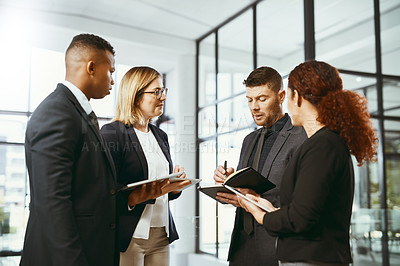 Buy stock photo Shot of a group of businesspeople using a digital tablet together in a modern office