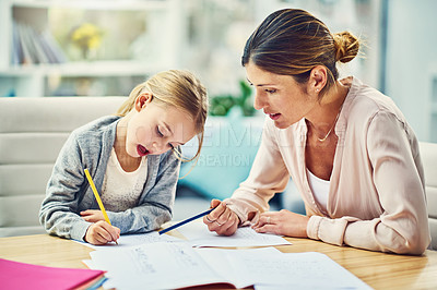 Buy stock photo Shot of a mother assisting her little daughter with schoolwork at home
