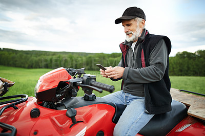 Buy stock photo Shot of a mature farmer using a cellphone while sitting on a quad bike in a field