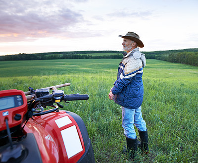 Buy stock photo Shot of a mature farmer standing alongside a quad bike on a field