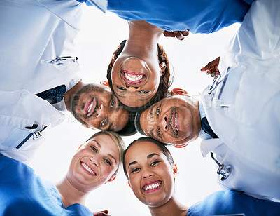 Buy stock photo Low angle portrait of a diverse team of doctors huddled together in unity