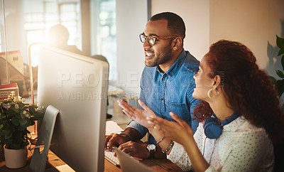 Buy stock photo Shot of a young businessman and businesswoman using a computer together during a late night at work