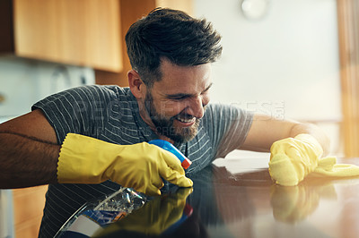 Buy stock photo Shot of a young man cleaning the kitchen counter at home