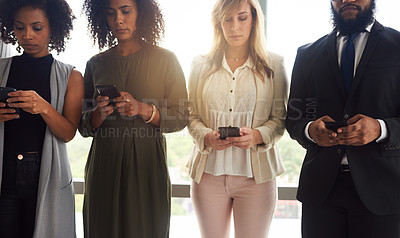 Buy stock photo Cropped shot of a group of young businesspeople using their cellphones while standing in a line in their office