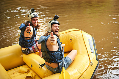 Buy stock photo Rearview portrait of two young friends giving you the thumbs up while sitting in their white water raft