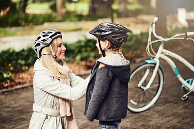 Buy stock photo Shot of a mother putting on her daughter's helmet before cycling