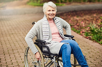 Buy stock photo Shot of a senior woman spending the day outdoors in her wheelchair