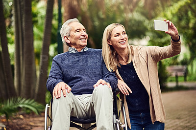 Buy stock photo Shot of a senior man in a wheelchair spending time outdoors with his daughter