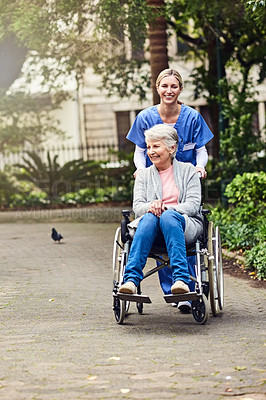 Buy stock photo Shot of a young nurse showing a senior woman in a wheelchair around the gardens