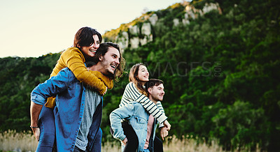 Buy stock photo Cropped shot of friends giving each other a piggyback ride outdoors