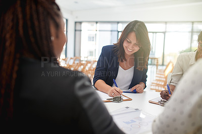 Buy stock photo Over the shoulder shot of a cheerful businesswoman signing a form to attend a seminar during the day