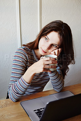 Buy stock photo Shot of an attractive young woman looking thoughtful while working at home