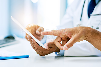 Buy stock photo Shot of an unrecognizable doctor and patient looking at test results on a digital tablet inside of a hospital during the day