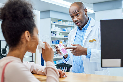 Buy stock photo Shot of a pharmacist assisting a young woman who is feeling unwell in a chemist