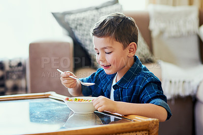 Buy stock photo Portrait of an adorable little boy having cereal at home