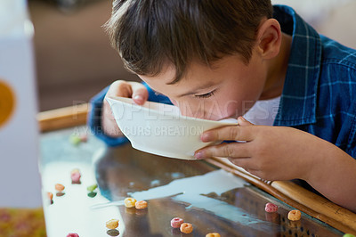Buy stock photo Shot of an adorable little boy drinking his cereal from a bowl at home