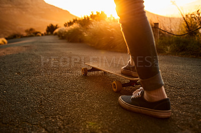 Buy stock photo Cropped shot of an unrecognizable woman out skating at sunset