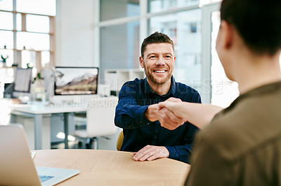 Buy stock photo Cropped shot of two young businesspeople shaking hands during a meeting in an office