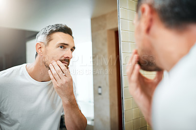 Buy stock photo Shot of a mature man going through his morning routine in the bathroom at home