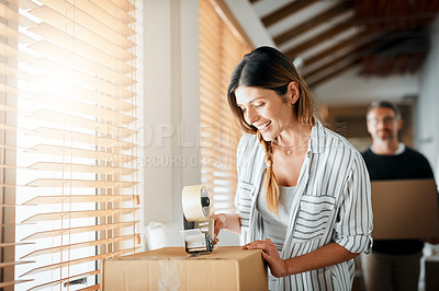 Buy stock photo Cropped shot of a woman taping up boxes in preparation to move house