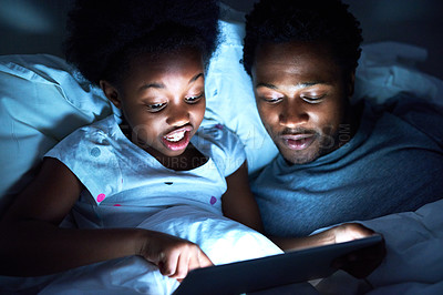 Buy stock photo Cropped shot of a handsome young man using a tablet to read his daughter a bedtime story