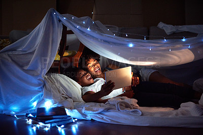 Buy stock photo Cropped shot of an attractive young woman using a tablet to read her daughter a bedtime story