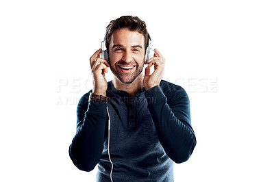 Buy stock photo Studio portrait of a handsome young man using headphones against a white background