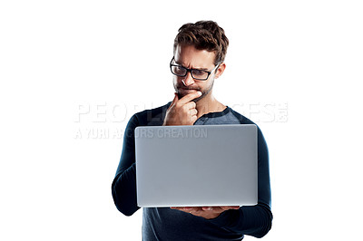 Buy stock photo Studio shot of a handsome young man using a laptop and looking confused against a white background