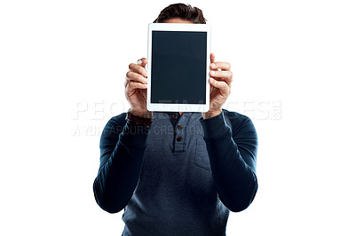 Buy stock photo Studio shot of a young man holding a digital tablet with a blank screen against a white background