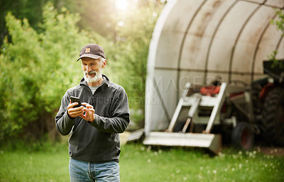 Buy stock photo Shot of a mature man using a mobile phone while working on a farm