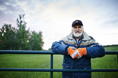 Buy stock photo Portrait of a mature man standing at the fence of a farm