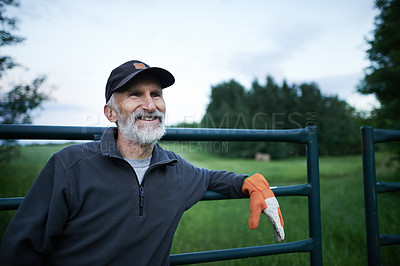 Buy stock photo Shot of a mature man standing at the fence of a farm