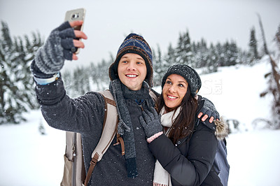 Buy stock photo Cropped shot of a man taking a selfie with his girlfriend while out on the snow