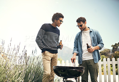 Buy stock photo Shot of two men drinking beer while cooking food on a barbecue grill outside