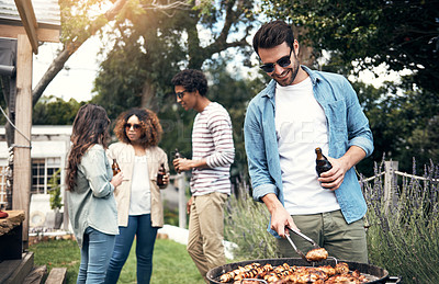Buy stock photo Shot of a young man cooking food on a barbecue grill at a party with friends