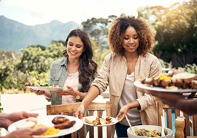 Buy stock photo Shot of two women having a meal together with friends outdoors