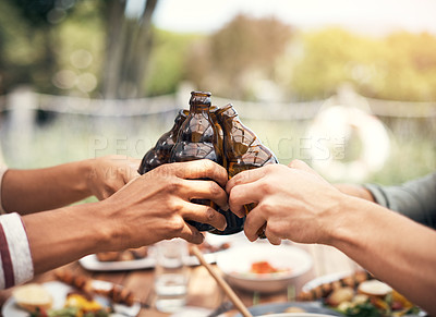 Buy stock photo Closeup shot of a group of friends toasting with beers while having a meal together outdoors